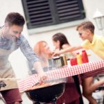 cooking meat on barbecue grill for his family at summer