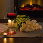 wine and white roses candle light