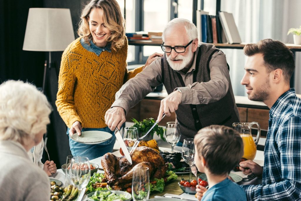grandfather cutting turkey for family on thanksgiving dinner