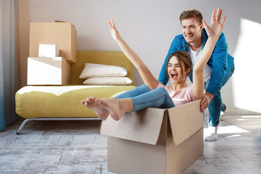 Young family couple bought or rented their first small apartment. Cheerful happy people having fun. She sit in box and scream. Guy move her. Moving and unpacking.